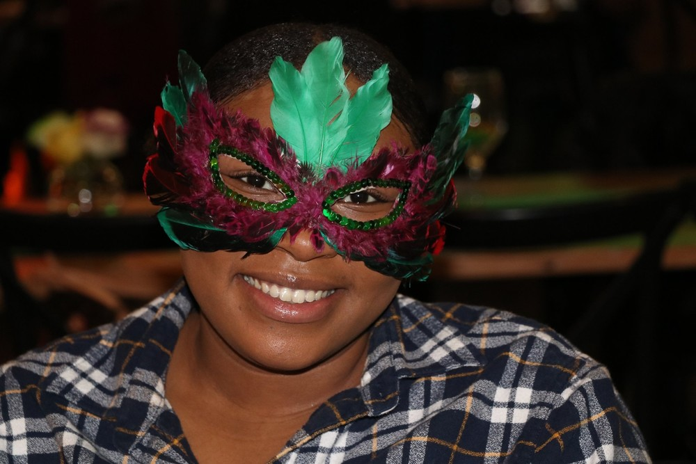 resident smiling with mardi gras mask on at banquet